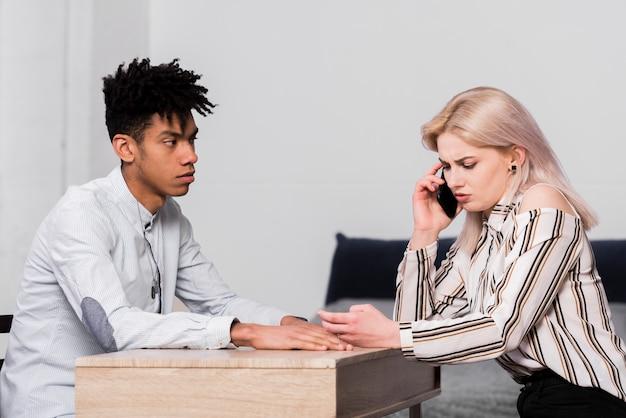 Подозрительный человек смотрит на свою подругу разговаривает по мобильному телефону
