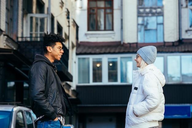お互いを見て彼のポケットに手を持つ若い異人種間のカップルの笑顔