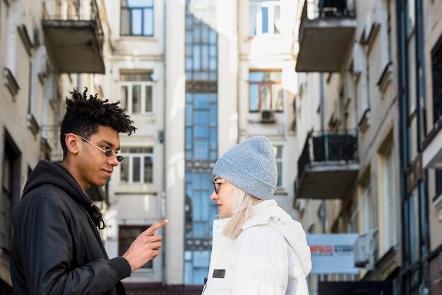 若い異人種間の若いカップル立っている顔の建物の下に立っている