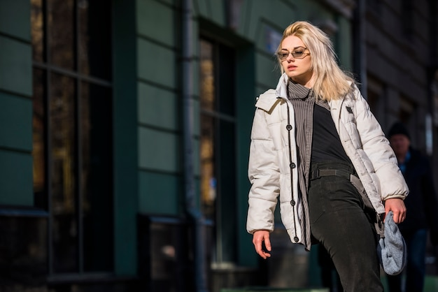 Портрет белокурой современной молодой женщины стоя перед зданием