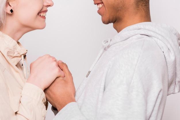 異人種間の若いクーペ互いの白い背景で隔離の手を握って