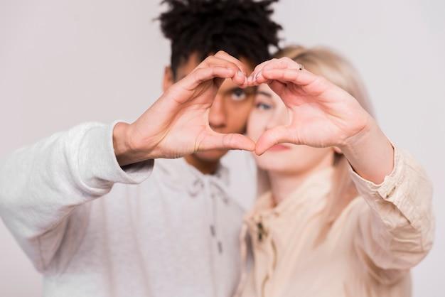 白い背景で隔離の手でハートを作る異人種間の若いカップル