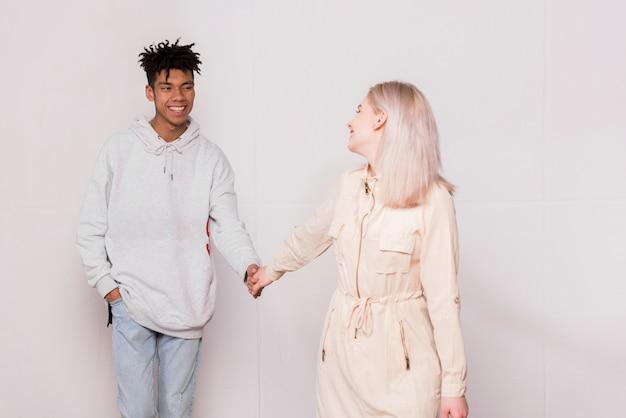白い背景に対して彼女のボーイフレンドを見て彼女のボーイフレンドの手を握って幸せな若い女
