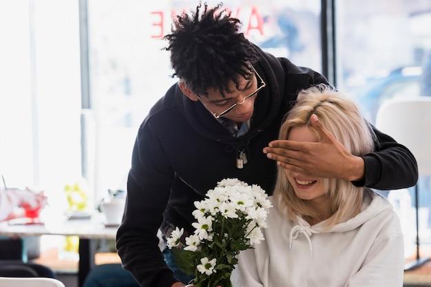 白い花の花束を与えている間彼女のガールフレンドの目を隠しているボーイフレンド