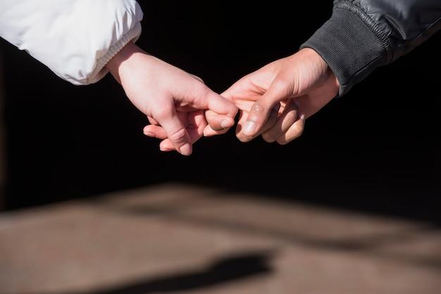 お互いの指を持っているカップルの手のクローズアップ