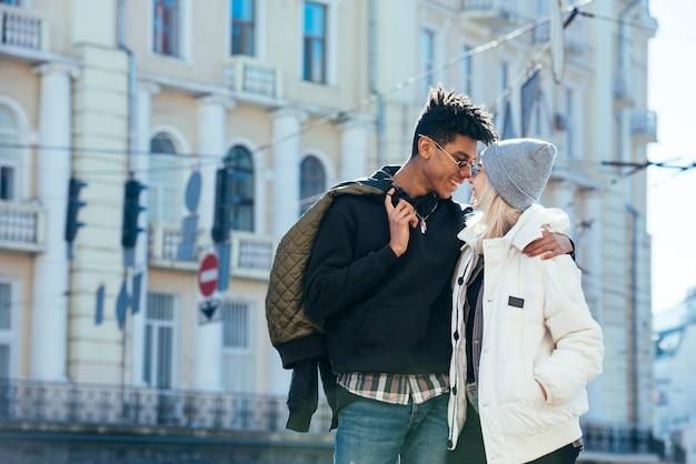 建物の前に愛する異人種間の若いカップルの立っています。