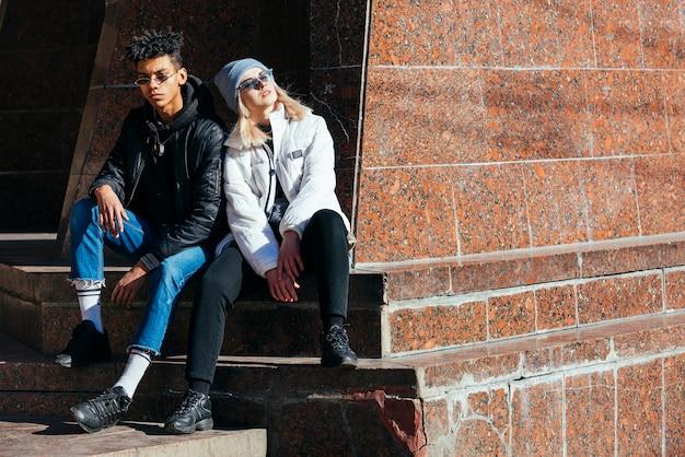 屋外に座っているファッショナブルな異人種間の若いカップルの肖像画