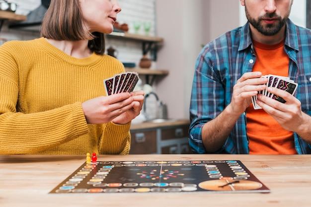 若いカップルが木製の机の上のボードゲームをプレイ