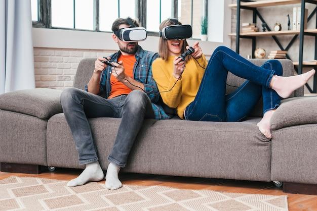 ビデオゲームをプレイ仮想現実の眼鏡をかけている若いカップル