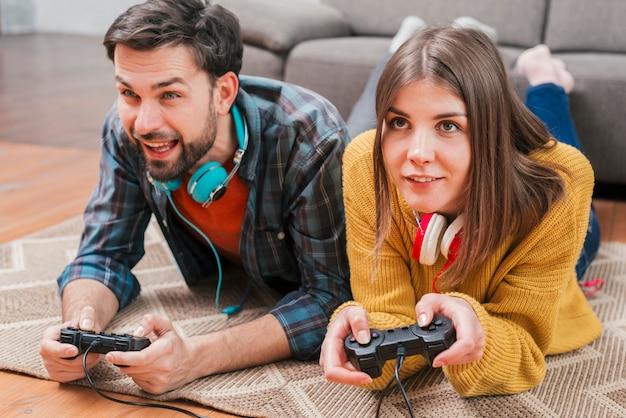 Молодая пара лежит на коврике и играет в видеоигру