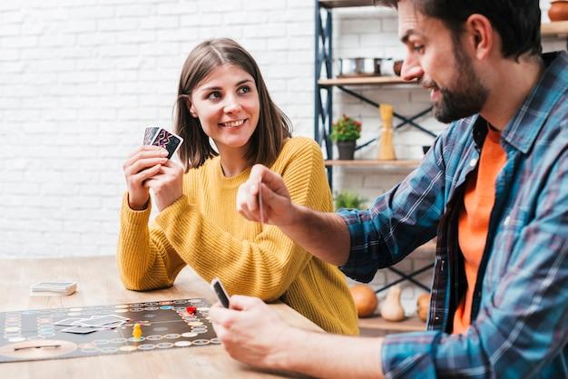 若いカップルが木製のテーブルの上のボードゲームをプレイ