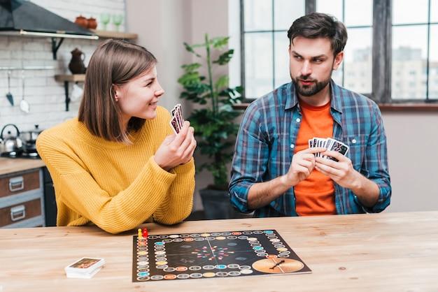 Молодая пара играет в настольную игру на кухне
