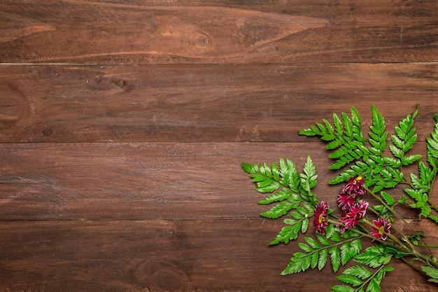 木製の背景の葉とピンクの花