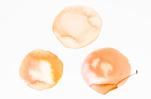 オレンジ色の水彩画のしみデザインの白い背景の上のテクスチャ