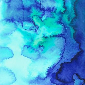 抽象的なブルーとターコイズブルーの水彩画のしみを描いた背景