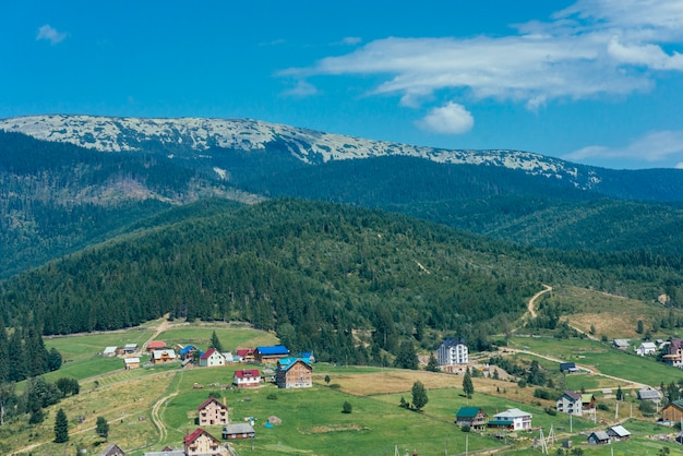 牧草地や家々とアルプスの牧歌的な山の風景