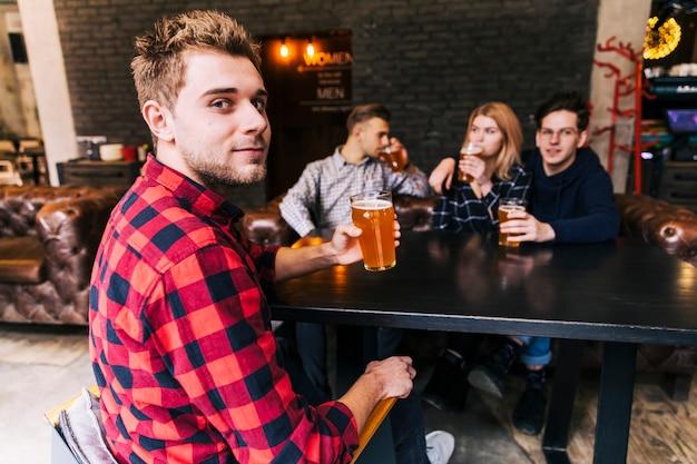 Портрет мужчины, держа бокал пива, сидя с друзьями, глядя на камеру