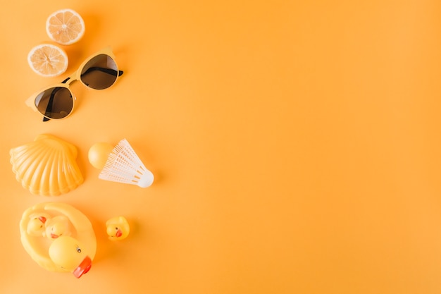 Половинки апельсинов; солнцезащитные очки; пластиковый шар; волан; гребешок и резиновая утка на цветном фоне