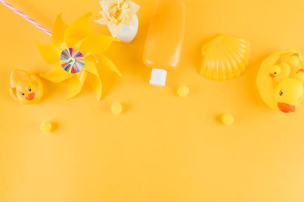 ゴム製のアヒル;風車;日焼け止めローションボトル。黄色の背景に小さなポンポンとホタテ