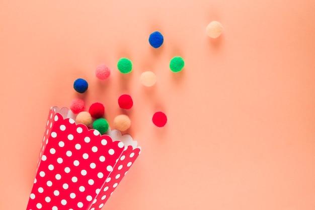 桃色の背景にこぼれたカラフルな糸のボールと水玉コーン