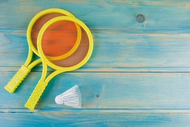 黄色のプラスチック製のテニスラケットと羽根青緑色のターコイズブルーの机の上
