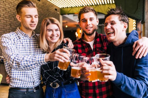 Группа друзей звонит пивные бокалы в пабе