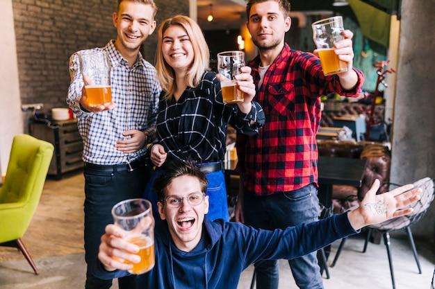 ビールグラスを手で押し笑顔の友達の肖像画を祝う