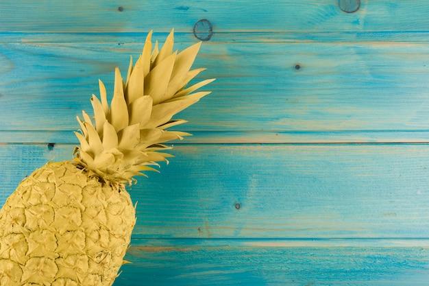 ターコイズブルーのテーブルに塗られたパイナップルの俯瞰