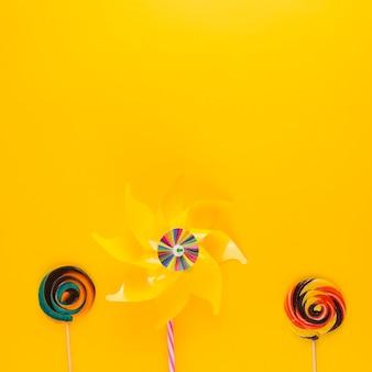 黄色の背景に渦巻きキャンディーと風車