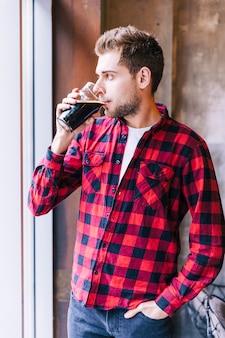 ビールのグラスを飲むポケットに手を持つ若い男のクローズアップ