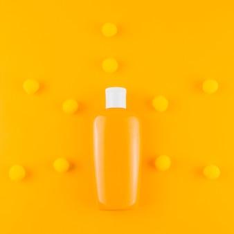 オレンジ色の背景に糸のポンポンボールと日焼け止めボトル