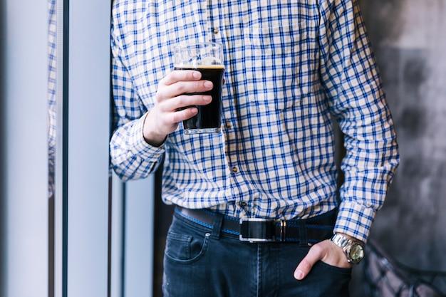 ビールのグラスを保持しているポケットに手を持つ男の中央部