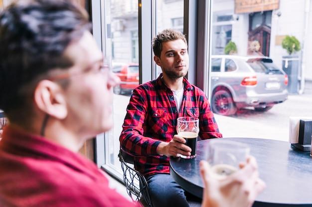 若い男がパブのレストランで彼の友達とビールを飲む