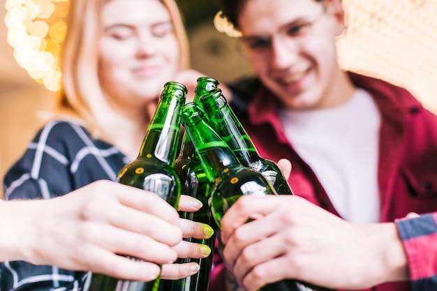 緑色のビール瓶を乾杯の友人のクローズアップ