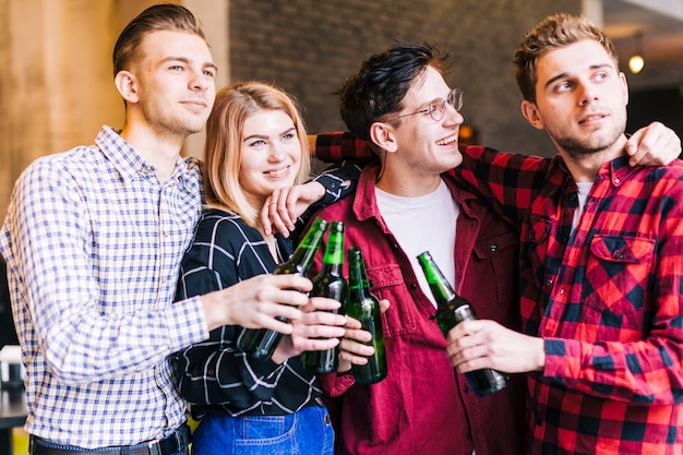 Счастливые улыбающиеся друзья держат зеленые пивные бутылки в руке