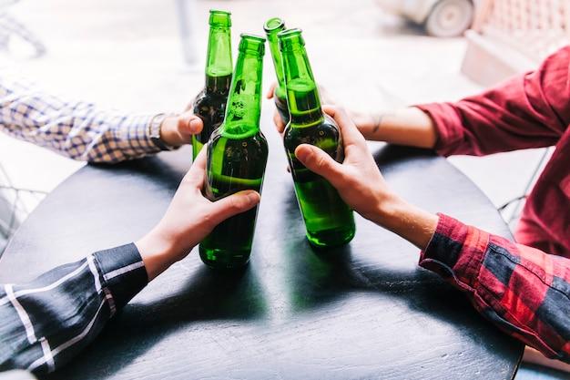 木製のテーブルの上にビール瓶を持って友達のクローズアップ