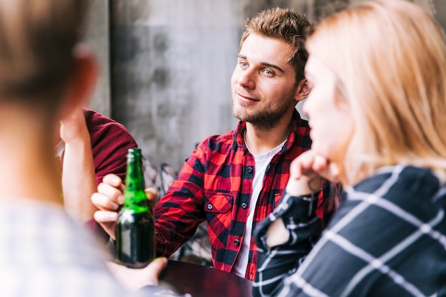 彼の友人と一緒に座って手にビール瓶を持って笑顔の若い男