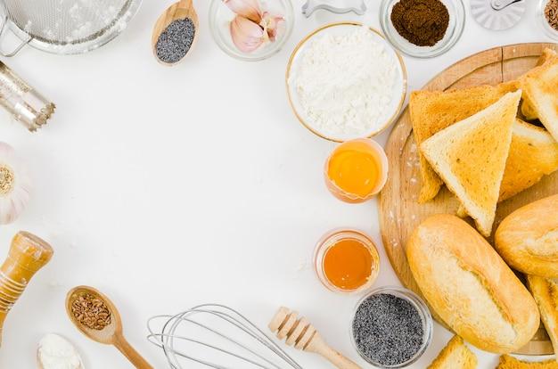 Хлеб ручной работы с ингредиентами и посудой на кухне