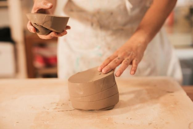 木製のテーブルに粘土を準備する男のクローズアップ