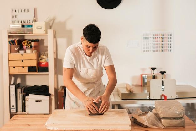 ワークショップで木の板に粘土を混練職人の手のクローズアップ