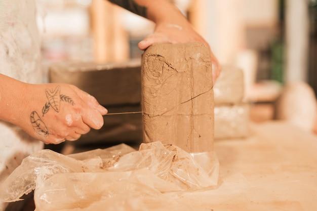 木のテーブルにスレッドで粘土を切る女性の手のクローズアップ