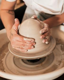 陶器のホイールに取り組んでいる手のクローズアップ