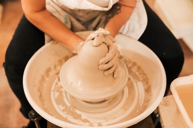 陶芸家は彼女の陶器の輪で粘土の鍋を作ることに取り組んでいます