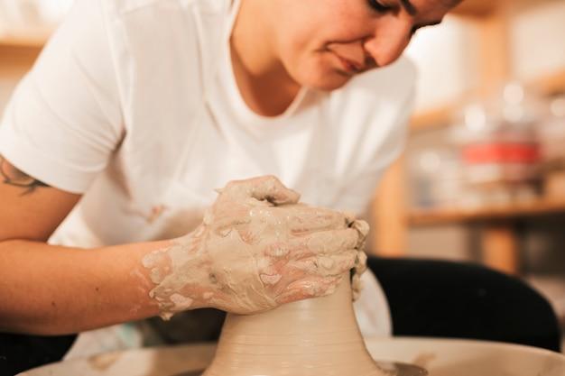 陶器のホイールに粘土に詳細を与える女性職人のクローズアップ