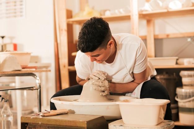 陶器のホイールに濡れた粘土の塊に形をする女性の陶芸家
