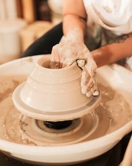 女性陶芸家の手は陶器のホイールになります
