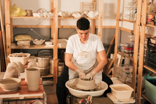 新しい陶磁器の鍋を作成する女性の陶工