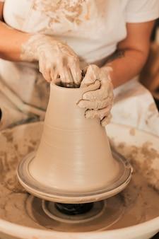 Крупный план делает горшок с глиной на гончарном круге
