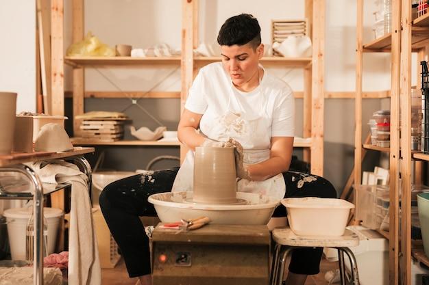 陶器のホイールに取り組んでいる女性の陶工