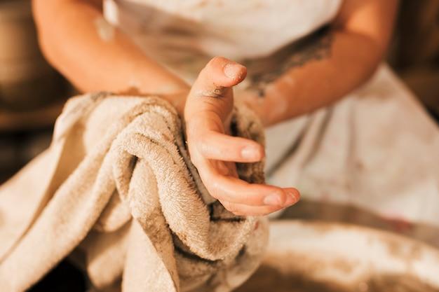 Крупный план женского гончара, чистящего ее руку салфеткой